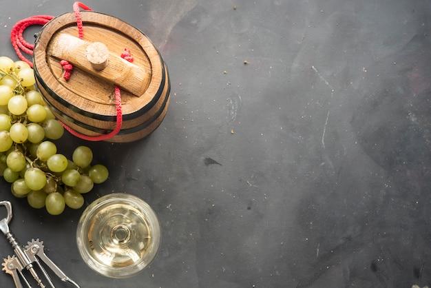 Natura morta con vino bianco, bottiglia e botte su sfondo nero