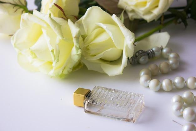 Natura morta degli oggetti della donna di modo su bianco. concetto di trucco femminile. rose bianche, profumo e ombra rosa, rossetto, perle