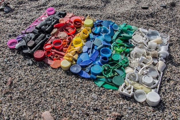 Natura morta degradata di tappi di plastica e diversi pezzi di plastica trovati sulla spiaggia, colore sfumato delle parti in plastica
