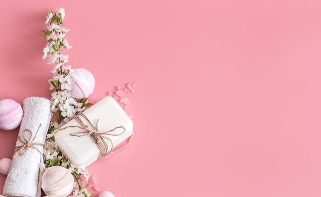 Natura morta della stazione termale su fondo rosa con i fiori della molla