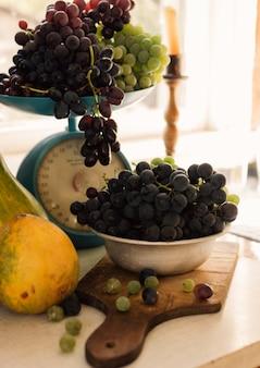 Natura morta di autunno con le zucche e l'uva sulle scale e in una ciotola del metallo su una tavola bianca di legno. concetto di vendemmia autunnale.