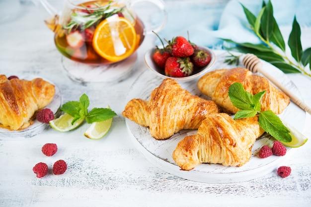 Natura morta di croissant e tè della bacca freschi di mattina in una teiera di vetro su un fondo di legno bianco. foto orizzontale di colazione.