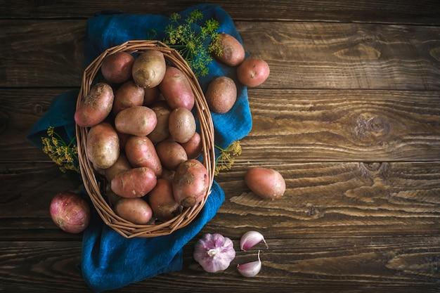Natura morta di estate delle patate mature su una tavola di legno.