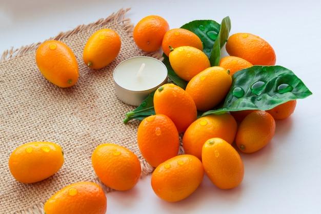 Natura morta di kumquat e candele su tela di sacco. sfondo rilassante. sfondo per il design spa.