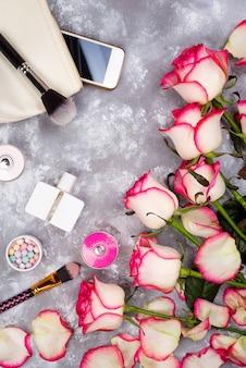 Natura morta di moda donna. moda femminile con bouquet di rose, cosmetici, telefono
