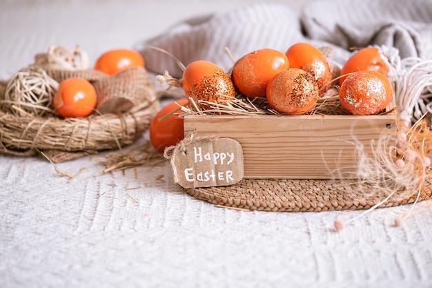 Natura morta di pasqua con uova d'arancia, decorazioni per le vacanze.