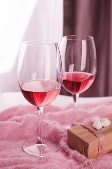 Natura morta di san valentino con le paia dei vetri di flauto di champagne, contenitore di regalo sull'estratto