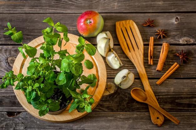Natura morta di utensili in legno con menta e mele