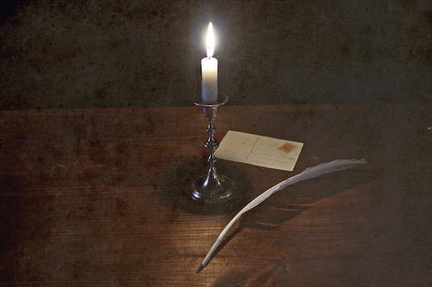 Natura morta di vecchia storia con la candela e la cartolina sul fondo di lerciume