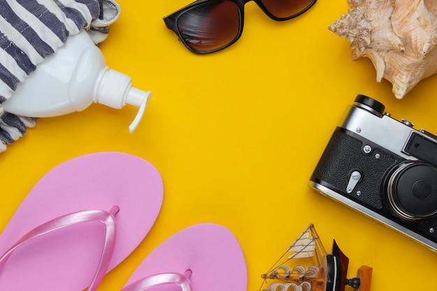 Natura morta estiva. accessori da spiaggia. infradito rosa alla moda, borsa, retro macchina fotografica, bottiglia di crema solare, occhiali da sole, conchiglia su fondo di carta gialla.