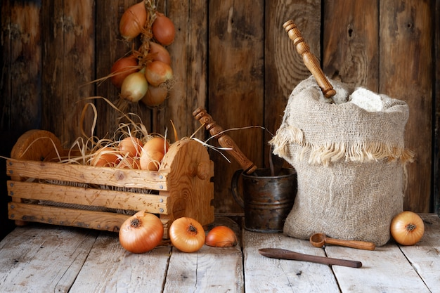 Natura morta, farina, cipolle, uova e spezie rustiche su una tavola di legno.