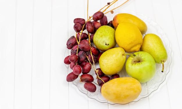 Natura morta frutta, mela, pera, mango, limone e datteri freschi su lastra di vetro.