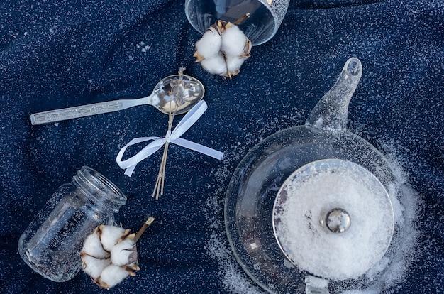Natura morta invernale, tra cui una teiera, un barattolo, un bicchiere, una pianta di cotone, piccoli fiori secchi