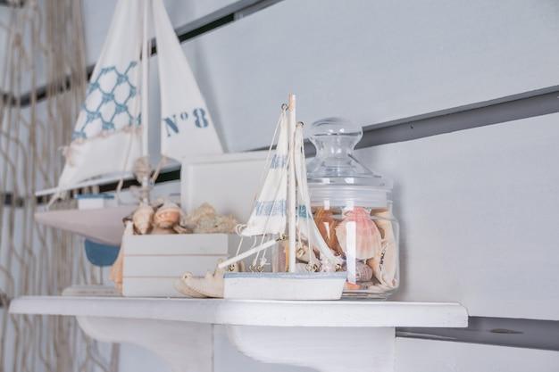 Natura morta marina con navi e pezzo di corallo. antica barca a vela modello toy. barche a vela, conchiglie.