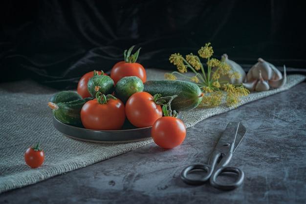 Natura morta rustica con verdure fresche: pomodori rossi, cetrioli verdi, aglio, aneto su uno sfondo scuro.