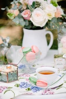 Natura morta spose mattina, piatto con una tazza di tè, bicchiere di champagne, fedi nuziali e bouquet di fiori