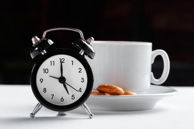 Natura morta, sveglia d'annata e tazza di caffè sulla tavola bianca