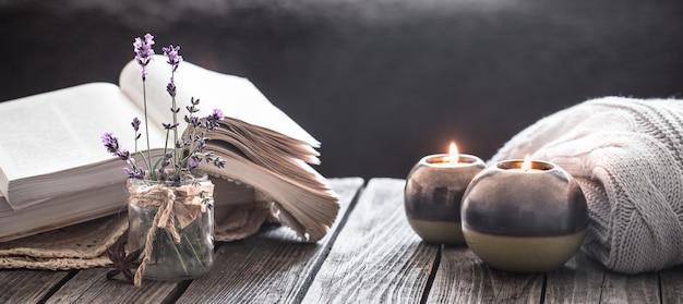 Natura morta un libro e una candela su una parete di legno
