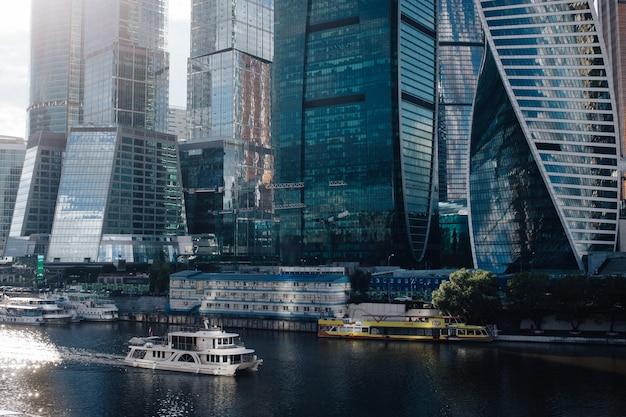 Nave a vela sul fiume di mosca nei pressi dei grattacieli di mosca-città con la riflessione delle nuvole