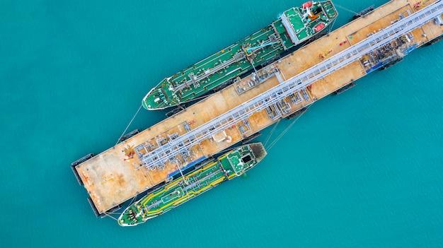 Nave cisterna di vista aerea che scarica al porto, olio dell'esportazione dell'importazione di affari con l'olio del trasporto della nave di autocisterna dalla raffineria sul mare.