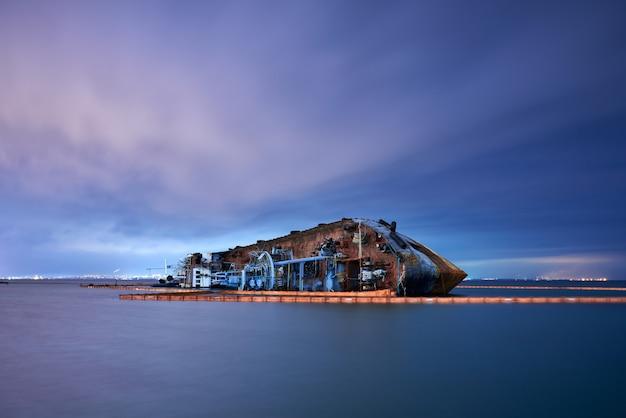 Nave cisterna distrutta su un mare silenzioso di notte