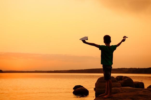 Nave di carta del lancio del ragazzino sull'acqua. bel tramonto estivo.