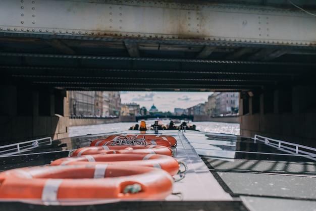 Nave passeggeri con passeggeri passa sotto il ponte sul fiume fontanka