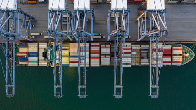 Nave porta-container che carica e che scarica nel porto marittimo profondo, vista superiore aerea dell'importazione e dell'esportazione logistiche di affari