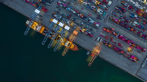 Nave porta-container che lavora di notte, logistica di esportazione di importazione di affari.