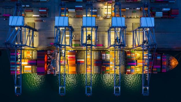 Nave porta-container che lavora di notte, logistica e trasporto di esportazione di importazione di affari