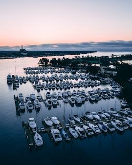 Navi bianche su un fiume circondato dal verde e dalle città durante il tramonto