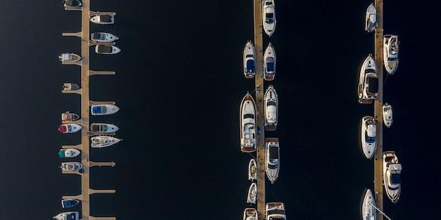 Navi, yacht, barche a vela e barche ormeggiate sul molo del fiume.