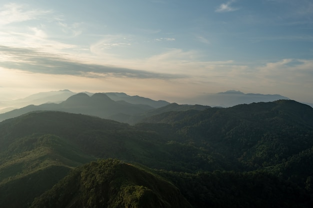 Nebbia, montagne, luce solare, belle cime montuose del punto di vista