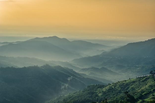 Nebbioso in montagna con cielo drammatico all'alba