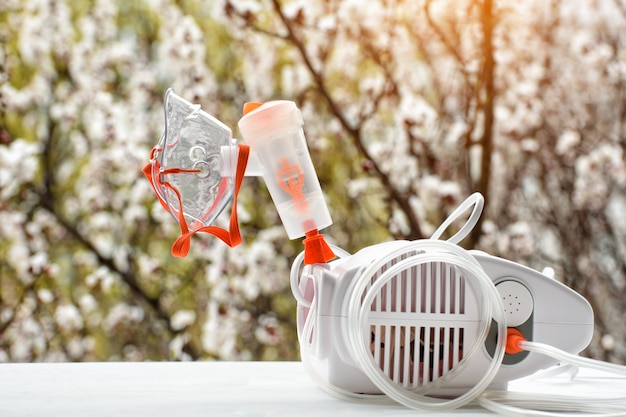 Nebulizzatore con una maschera sul di un albero sbocciante. esacerbazione di primavera