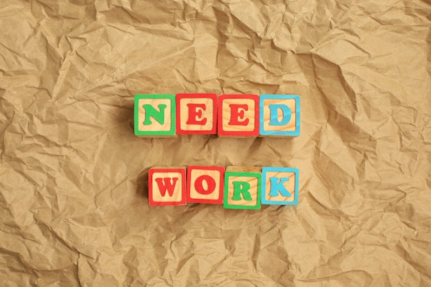 Necessario lavoro fatto da lettere di legno sulla parete di carta riciclata marrone spiegazzata.