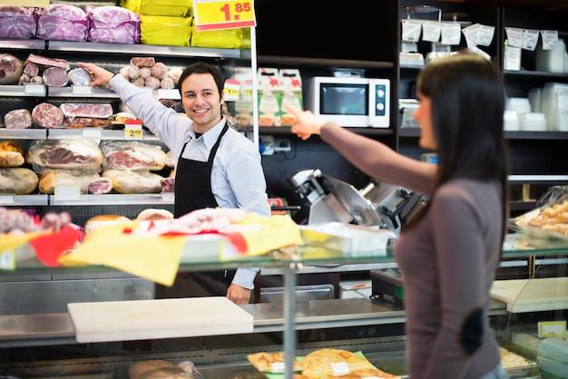 Negoziante al servizio di un cliente nel suo negozio di alimentari
