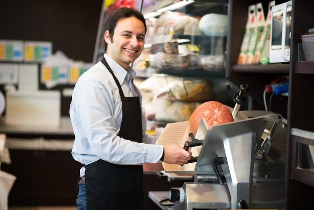 Negoziante che taglia carne affettata italiana in un negozio di alimentari