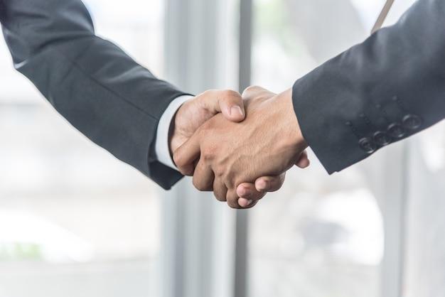 Negoziare gli affari, gli uomini d'affari si stringono la mano sul posto di lavoro.