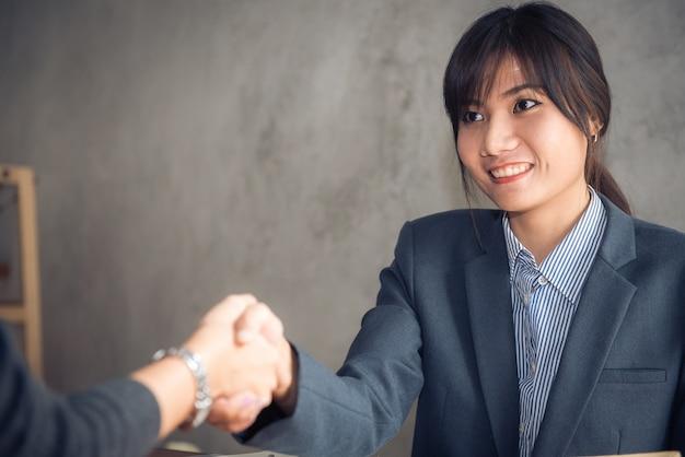 Negoziare le imprese, imprenditrice affari stretta di mano, felice con il lavoro, donna d'affari che sta godendo con il suo compagno di lavoro, handshake gesturing people connection deal concept. immagini di stile di effetti vintage.