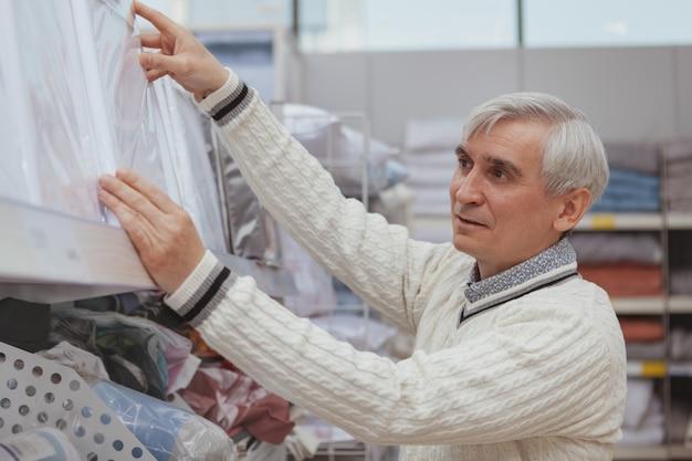 Negozio di beni anziano di acquisto a casa dell'uomo