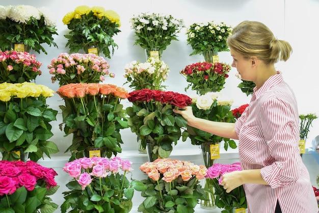 Negozio di fiori, la donna sceglie le rose nel negozio.