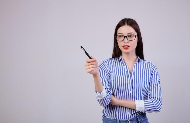 Nel è una piacevole giovane donna d'affari civettuola con capelli e occhiali castani. la donna tiene in mano una penna nera.