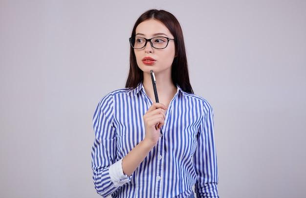 Nel è una piacevole giovane donna d'affari con i capelli scuri e gli occhiali per computer. la donna tiene in mano una penna nera. guardando lateralmente