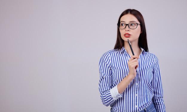 Nel è una piacevole giovane donna d'affari con i capelli scuri e gli occhiali per computer. la donna tiene in mano una penna nera. guardando pensosamente di lato