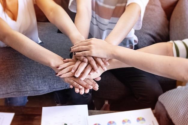 Nel fuoco selettivo delle mani dei giovani accatastate insieme, il collaboratore, per la fiducia e il successo dell'affare, unione, concetto di lavoro di squadra