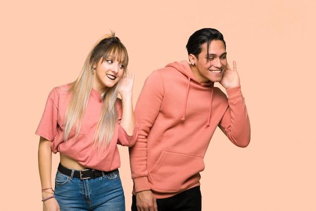 Nel giorno di san valentino coppia giovane ascoltando qualcosa mettendo la mano sull'orecchio su sfondo rosa