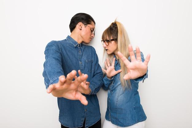 Nel giorno di san valentino coppia giovane con gli occhiali è un po 'nervosa e spaventata allungando le mani verso la parte anteriore