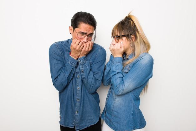 Nel giorno di san valentino coppia giovane con gli occhiali è un po 'nervosa e spaventata mettendo le mani in bocca