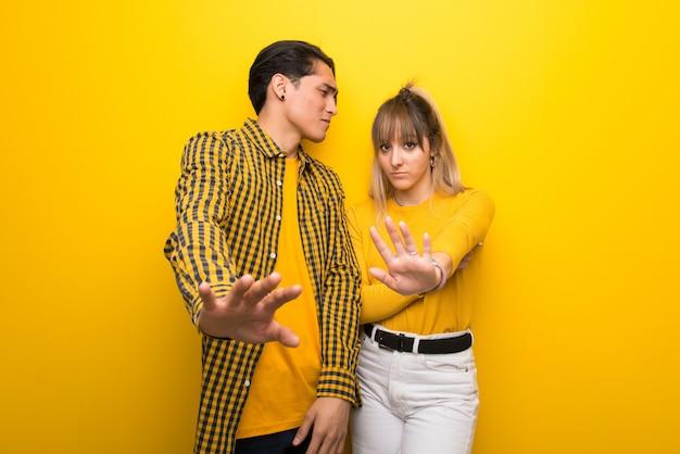 Nel giorno di san valentino coppia giovane su sfondo giallo vivace è un po 'nervoso e spaventato allungando le mani verso la parte anteriore